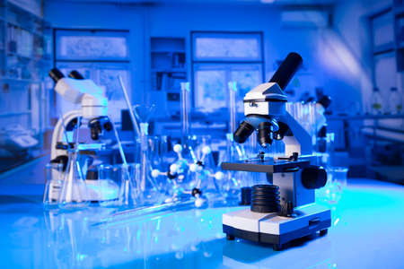 Laboratory investigations concerning covid pandemy. Microscope, glass tubes and beakers in the laboratory.