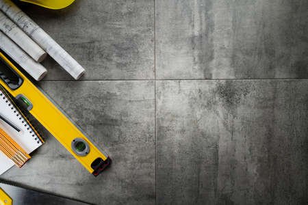 Contractor theme. Plans, tool kit of the contractor, yellow hardhat and libella. Gray tiles background.