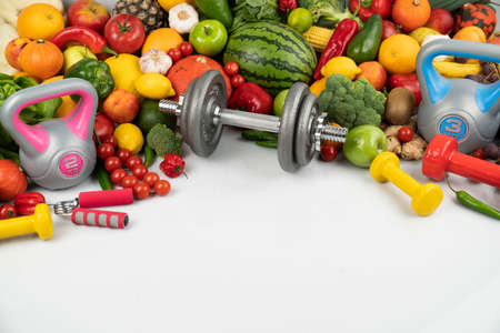 Fitness concept. Healthy nutrition: fruits and vegetables. Equipment for fitness exercises: weighing machine and dumbells. White background.