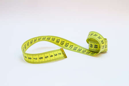 Yellow tape measure in meters and inches in a spiral Foto de archivo