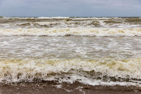 Dirty sea waves hitting the beach in stormy weather