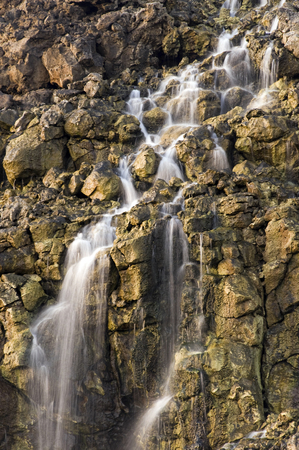 desalination: Brine falls from volcanic rock drop off to a runoff stream