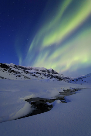 photons: Aurora Borealis over Skittendalstinden in Troms County, Norway. Auroras are the result of the emissions of photons in the Earths upper atmosphere.