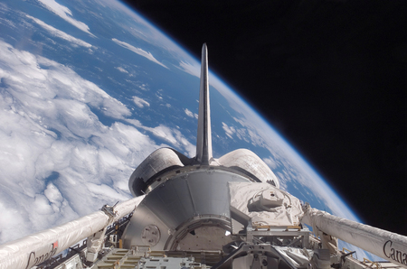 maneuvering: Space Shuttle Discovery backdropped by Earth