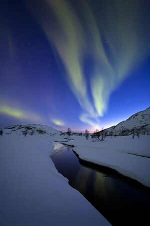 photons: Aurora Borealis over Skittendalen Valley and the Skittendalen River in Troms County, Norway. Auroras are the result of the emissions of photons in the Earths upper atmosphere.