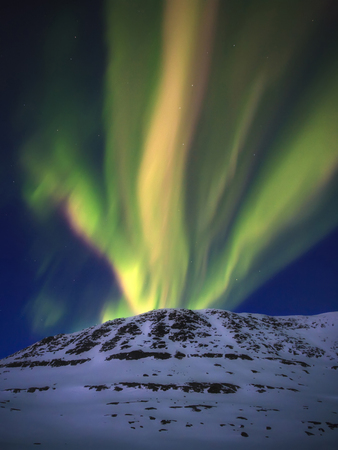 A fantastic eruption of Aurora Borealis over Toviktinden Mountain in Troms County, Norway. Auroras are the result of the emissions of photons in the Earths upper atmosphere. LANG_EVOIMAGES