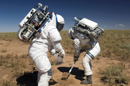 Two astronauts collect soil samples during Desert RATS activity in Arizona LANG_EVOIMAGES