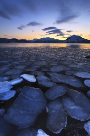 ice floes: A rare sight in Tjeldsundet, Troms County, Norway. Ice flakes drifting in the sunset looking towards the mountains on Tjeldoya Island. LANG_EVOIMAGES