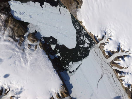 calved: August 16, 2010 - The ice island that calved off the Petermann Glacier in northwestern Greenland continues its slow migration down the fjord 11 days later. Although slivers of ice have loosened around its edges, the ice island has largely retrained its or