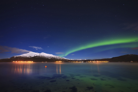 photons: Aurora over Tjeldsundet and Saetertinden Mountain in Troms County, Norway. Auroras are the result of the emissions of photons in the Earths upper atmosphere.