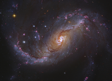 NGC 1672 is a prototypical barred spiral galaxy in the constellation Dorado, and differs from normal spiral galaxies in that the spiral arms do not twist all the way into the centre. Instead, they are attached to the two ends of a straight bar of stars en