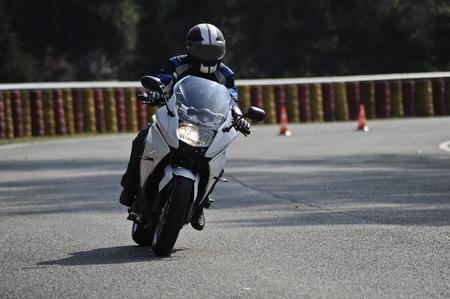 casco moto: motorista en la carretera con el casco y el asfalto mojado Foto de archivo