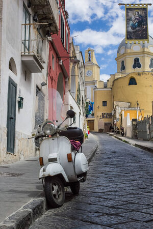 view of an alley on the island of Procida with the flag of the Virgin Mary and a wasp