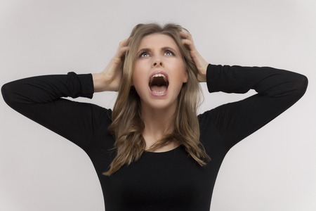 stressed girl screams with his hands through his hair photo