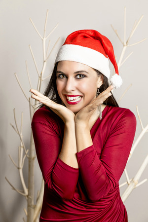 Beautiful girl with Christmas hat and red dress photo