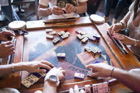 fila de personas: algunos jugadores de domin� en la mesa de edad Foto de archivo