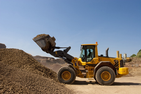 bulldozer in action in a big quarry Stok Fotoğraf