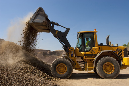 bulldozer in action in a big quarry Imagens