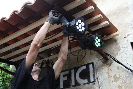 lighting technician: a man riding a spotlight for maintenance