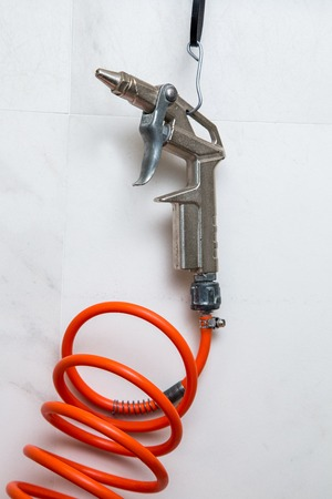 compressed air: gun for compressed air with wire hooked to a nail Stock Photo