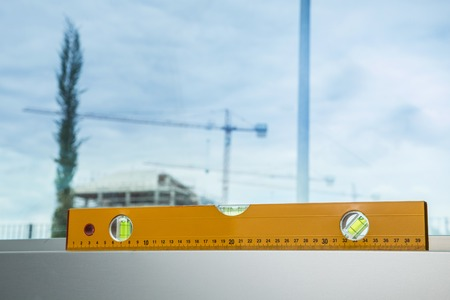 leveling instrument: yellow level with a construction yard with a crane Stock Photo