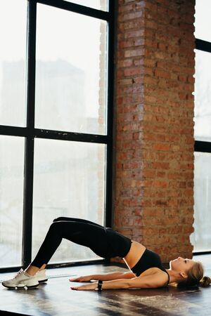 athletic girl in a t-shirt in black pants and white sneakers does a workout in a fitness studio on the floor. shows different sport poses. studio loft brick walls