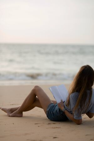 the brunette is lying on the beach in a shirt and denim shorts and reading