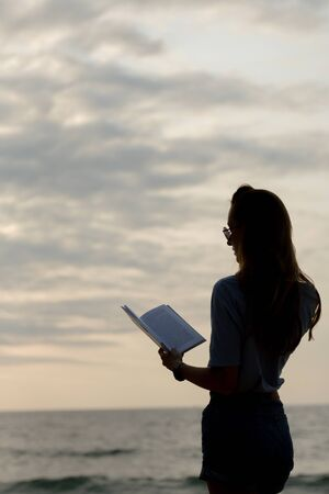 a silhouette of a beautiful girl in denim shorts and a blue shirt stands near the sea and reads