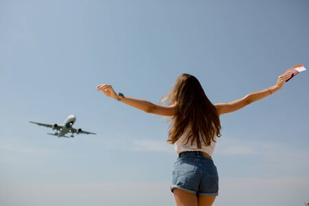 a slender girl in denim shorts and a white t shirt has her arms outstretched passport in hand near the