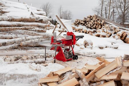 red woodcutter stands in the middle of split logs in winter next to the