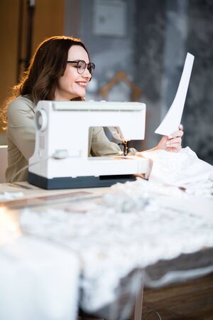 The seamstress happily looks at a sheet of paper with a dress pattern.