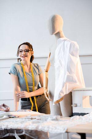 Female fashion designer chooses fabric color for next dress