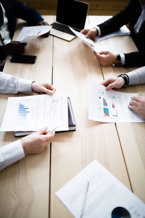 Hands of four businessmen of different nationalities with charts of company subsidiaries Stock Photo