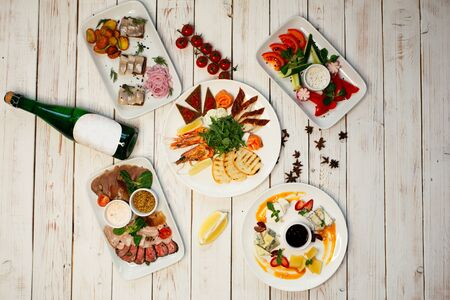 Set of meat and cheese snacks on plates. On the plates is a sauce for appetizers. Set of bar snacks and a bottle of champagne on a wooden background.