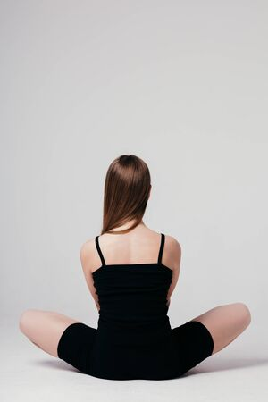A young girl in black sportswear sits with her back to the camera on a white background and meditates
