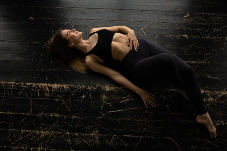 Beautiful girl lying on the floor and resting after doing yoga. Relaxed pose of the woman and looks out the window.