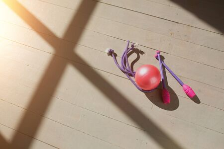 Pink gymnastic wands, pink ball and jump rope lying on the wooden floor in the rays of the rising sun. Bright light and shadow.