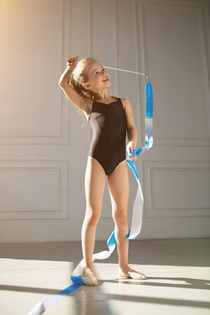 Beautiful little girl in a swimsuit standing with a gymnastics ribbon and exercising in the gym. The gymnast stands on white background.
