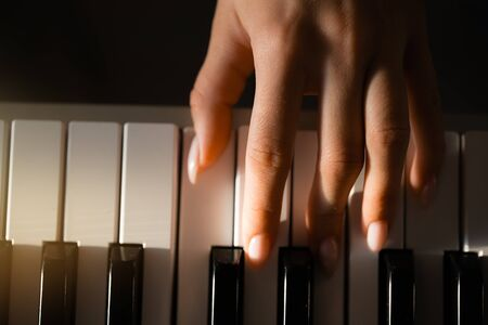 Close-up. A female hand performs a solemn chord on a piano in the rays of sunlight Imagens
