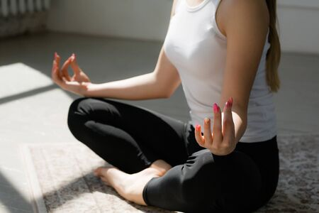 Close-up of a female body in lotus position. Girl meditates on the floor in the sun Stock fotó