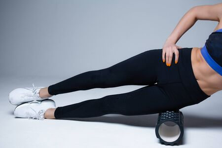 Close up of legs. Pilates trainer kneads the fascia of lateral muscles of the thigh with a massage roller before starting exercise