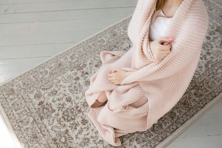 A female figure, wrapped in a pink blanket. Girl sits on home carpet in the apartment and heated. autumn atmosphere