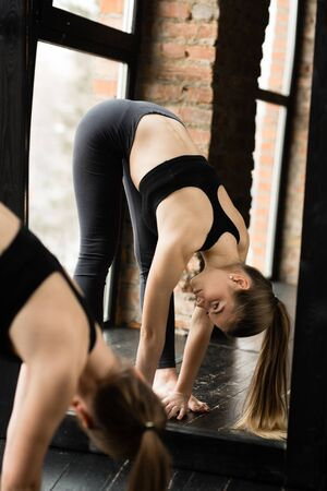 A young girl with long hair in sportswear doing yoga in the gym and making the tilt outstretched arms to the floor. Фото со стока