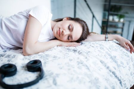A girl of European appearance sleeps on the bed next to the headphones. Fell asleep after listening to music and meditation