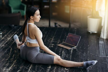 The girl is engaged in stretching on the twine. He spreads his legs to the side while sitting on the floor in front of the laptop