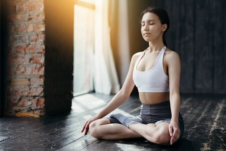 Beautiful Asian girl meditates in lotus position on the floor near a large window in the sun