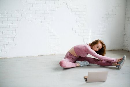 Yoga trainer sits in studio on the floor and is engaged in stretching longitudinal splits in video tutorial on the laptop