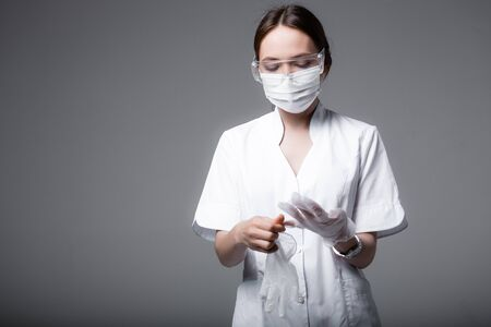 The girl the doctor in a white coat, a medical mask and safety glasses. Doctor puts on protective gloves