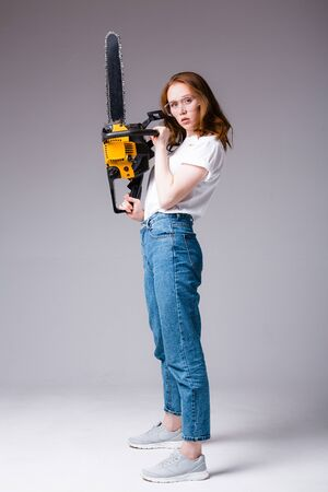 Sexy redhead girl in safety glasses in a white T-shirt and jeans holds a chainsaw near her face and looks at the camera. Foto de archivo