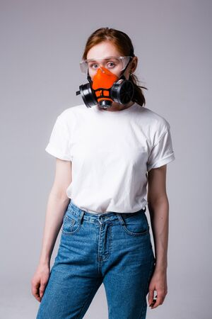 Portrait of red-haired girl in white T-shirt standing in respirator and safety glasses and looking at camera on a gray background